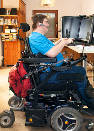 sitting in a multifunctional wheelchair using a computer with a touch screen and wireless headset, side view